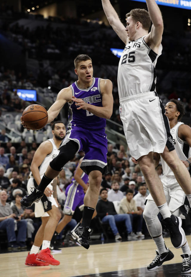 Sacramento Kings guard Bogdan Bogdanovic (8) drives to the basket past San Antonio Spurs center Jakob Poeltl (25) during the first half of an NBA basketball game in San Antonio, Friday, Dec. 6, 2019. (AP Photo/Eric Gay)