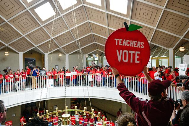 <p>Teachers and supporters hold signs during a 'March For Students And Rally For Respect' protest at the North Carolina State Assembly, on the first day of the state's legislative session, in Raleigh, N.C., on Wednesday, May 16, 2018. (Photo: Charles Mostoller/Bloomberg via Getty Images) </p>