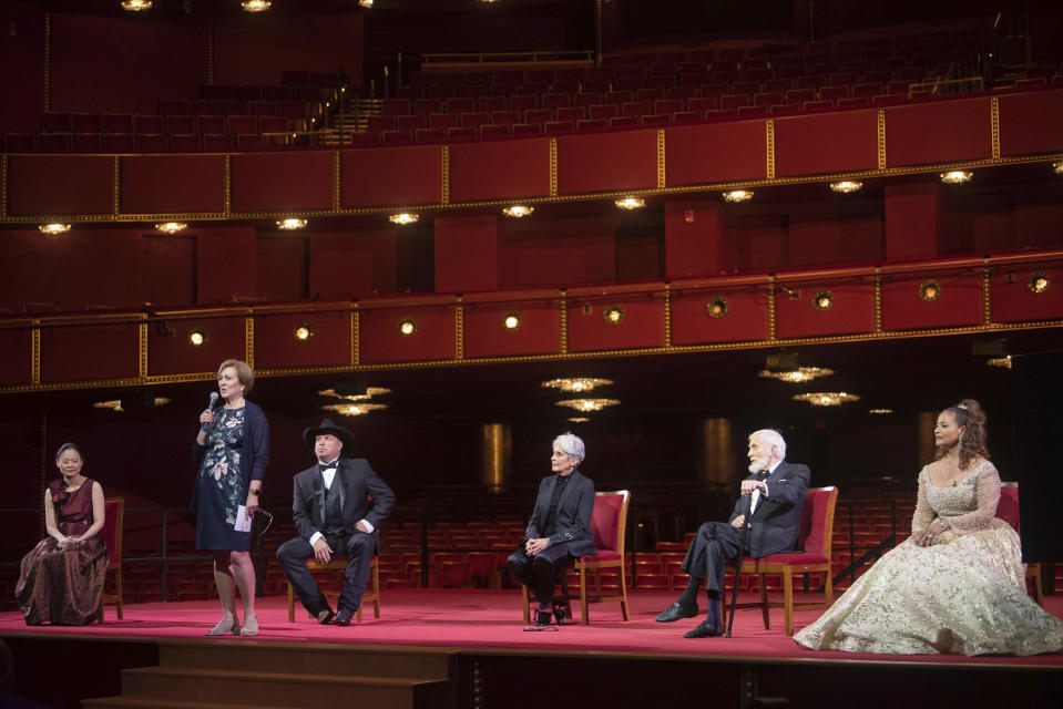 Kennedy Center President Deborah F. Rutter, second from left, speaks during a press event with the 2020 Kennedy Center honorees, from left, violinist Midori, country singer-songwriter Garth Brooks, singer-songwriter and activist Joan Baez, actor Dick Van Dyke, and choreographer, and actress Debbie Allen during the 43nd Annual Kennedy Center Honors at The Kennedy Center on Friday, May 21, 2021, in Washington. (AP Photo/Kevin Wolf)