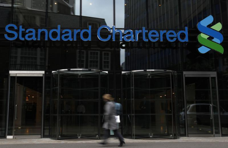 A woman walks past a Standard Chartered bank in London