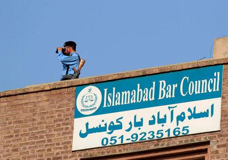 A policeman looks through binoculars from the rooftop of the National Accountability Bureau (NAB) court in Islamabad, Pakistan October 19, 2017. REUTERS/Faisal Mahmood