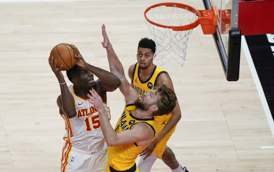 Atlanta Hawks' Clint Capela (15) shoots and scores against Indiana Pacers' Domantas Sabonis (11) during the second half of an NBA basketball game against the Indiana Pacers on Sunday, April 18, 2021, in Atlanta. (AP Photo/Brynn Anderson)