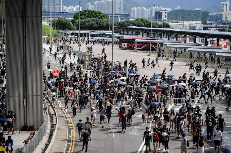 Protesters run from police at the bus terminal at Hong Kong International Airport on September 1, 2019. — AFP pic