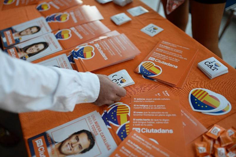 A person takes a sticker with the Spanish, Catalan and European flags on it during a Ciutadans (Citizens) political party campaign meeting for the upcoming Catalan regional elections, in Barcelona (AFP Photo/Josep Lago)