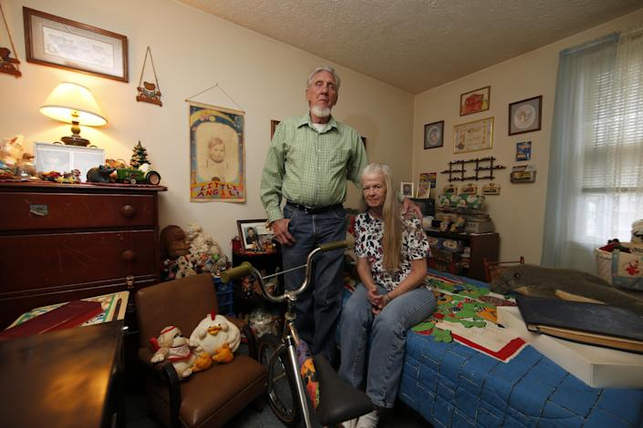 This photo taken April 29, 2014, shows Victor Shoemaker Sr., and his wife Nettie Shoemaker posing for a photograph in their son's bedroom in their home in Leesburg, Va. The bedroom has been left the way it was when twenty years ago Victor Dwight Shoemaker Jr., vanished while playing with two cousins along a West Virginia mountainside, his parents hold the belief that their only child is still alive. The boy known as J.R. had been in the woods behind his grandfather's mobile home in Hampshire County when two cousins emerged without him on May 1, 1994. No trace of him was ever found. (AP Photo/Alex Brandon)