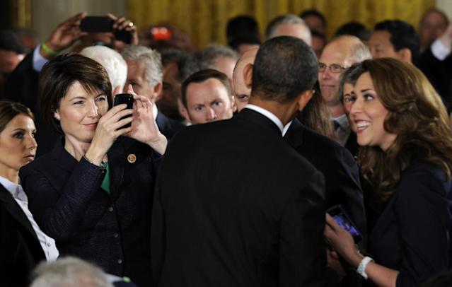 Rep. Cathy McMorris Rodgers, R-Wash., left, takes a photo of President Barack Obama following a ceremony the East Room of the White House in Washington, Wednesday, May 21, 2014, where the president honored the NFL Super Bowl champion Seattle Seahawks football team. The Seahawks defeated the Denver Broncos in Super Bowl XLVIII. Rep. Jaime Herrera Beutler, R-Wash. is at right. (AP Photo/Susan Walsh)