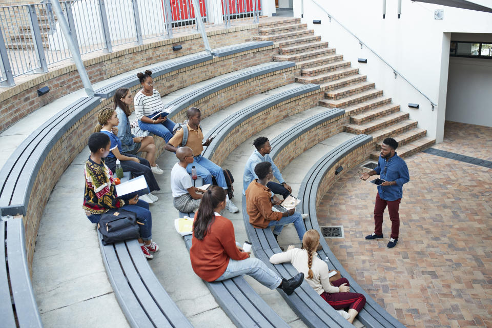 High angle view of male professor teaching young multi-ethnic students sitting on amphitheater steps at community college campus