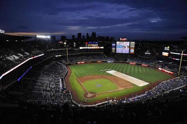 Grounds crewmen cover the infield during a weather delayed start to the New York Mets and Atlanta Braves baseball game, Monday, June 17, 2013, in Atlanta. (AP Photo/John Amis)