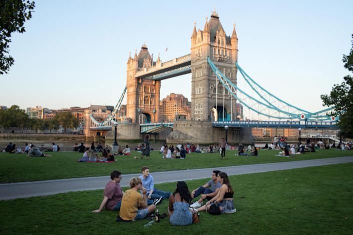 """LONDON, Sept. 14, 2020  -- People sit on the lawn at Potters Fields Park in front of Tower Bridge in London, Britain, on Sept. 14, 2020.   In order to curb the rise in coronavirus cases, tough new limits on social gatherings came into force in Britain on Monday, meaning that in most regions, it is now illegal for groups of more than six to meet up. The """"rule of six"""" kicked off at midnight across England, Wales and Scotland in the latest push to curb the recent surge in coronavirus infections. (Photo by Tim Ireland/Xinhua via Getty) (Xinhua/Tim Ireland via Getty Images)"""