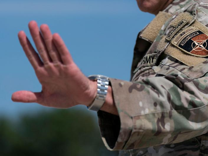 The hand of US General Scott Miller is raised towards the camera. He is wearing his army uniform.
