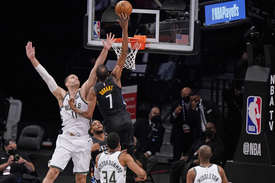 Milwaukee Bucks center Brook Lopez (11) tries to block Brooklyn Nets forward Kevin Durant (7) as Durant shoots during the first half of Game 2 of an NBA basketball second-round playoff series, Monday, June 7, 2021, in New York. (AP Photo/Kathy Willens)
