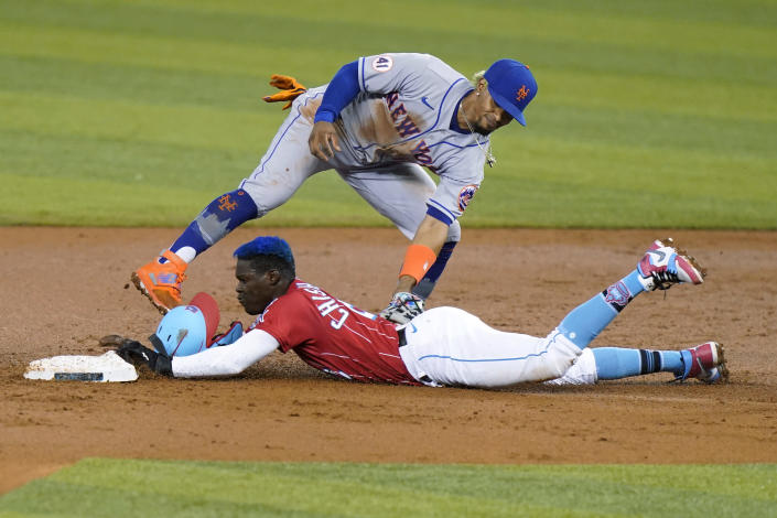 Miami Marlins' Jazz Chisholm Jr. is tagged out by New York Mets shortstop Francisco Lindor on an attempted steal of second during the first inning of a baseball game Friday, May 21, 2021, in Miami. (AP Photo/Lynne Sladky)