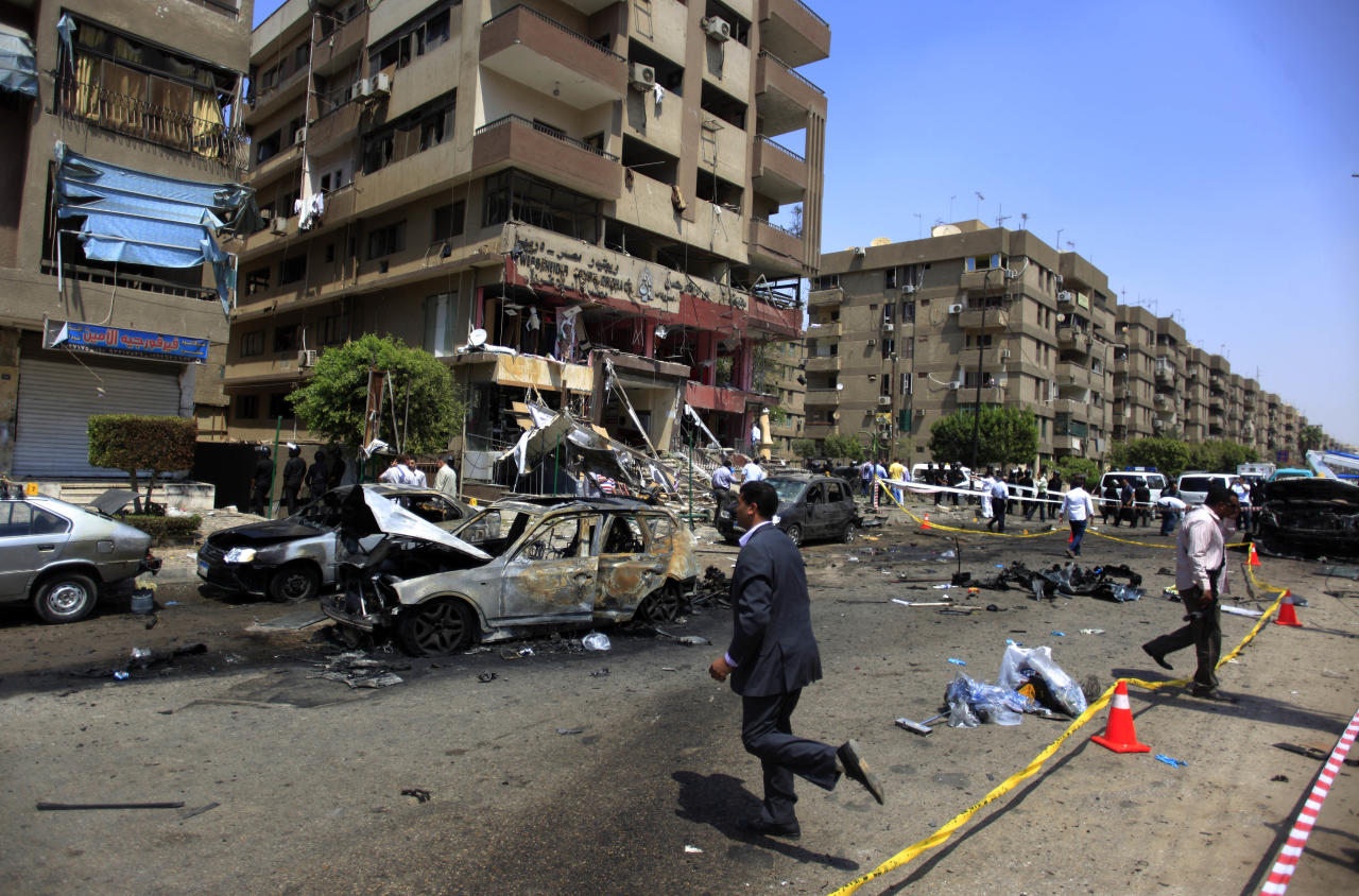"""Egyptian security officers gather at the scene of a bomb attack targeting the convoy of Egypt's Interior Minister Mohammed Ibrahim, in Nasr City, Cairo, Egypt, Thursday, Sept. 5, 2013. A """"large"""" explosive targeted the convoy of Egypt's interior minister Thursday in Cairo's eastern Nasr City district, the first attack on a senior government official since a coup toppled the country's Islamist president two months ago. (AP Photo/Khalil Hamra)"""