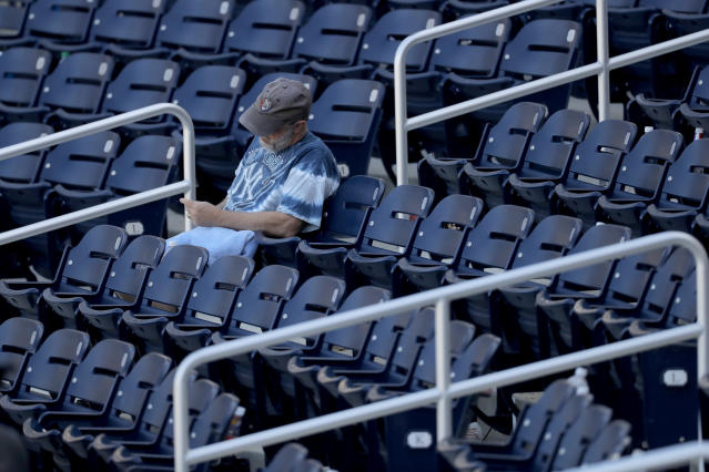 A lingering fan sits behind home plate after a spring training baseball game between the New York Yankees and the Washington Nationals, Thursday, March 12, 2020, in West Palm Beach, Fla. (AP Photo/Julio Cortez)