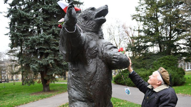 A former Polish soldier touches a statue of Wojtek the bear.