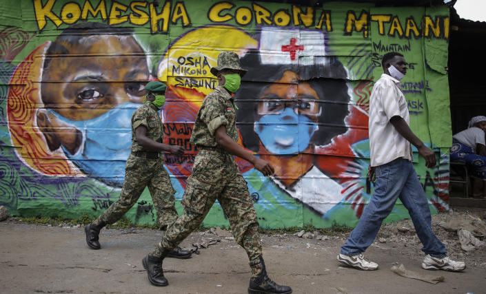 """Members of the National Youth Service walk past an informational mural about the coronavirus with words in Swahili reading """"Stop corona in the neighborhood"""", painted by graffiti artists from the Mathare Roots youth group, in the Mathare slum, or informal settlement, of Nairobi, Kenya Thursday, April 30, 2020. (AP Photo/Brian Inganga)"""