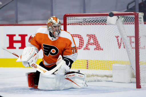 Philadelphia Flyers' goaltender Carter Hart watches as the puck flies away from him during the first period of an NHL hockey game against the Pittsburgh Penguins, Wednesday, Jan. 13, 2021, in Philadelphia. (AP Photo/Chris Szagola)