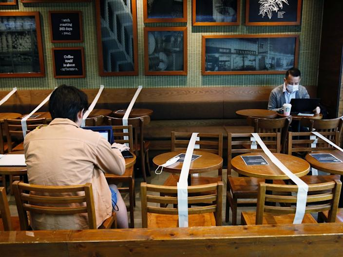 """Tables and chairs taped up to maintain social distancing at a Starbucks coffee shop in Hong Kong, on April 2, 2020. <p class=""""copyright"""">Tyrone Siu/Reuters</p>"""