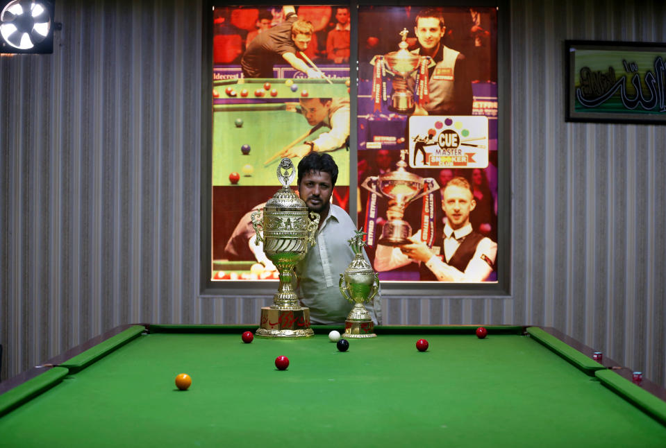 Mohammad Ikram, who play snooker with his chin, poses for photographer with his trophies at a local snooker club in Samundri town, Pakistan, Sunday, Oct. 25, 2020. Ikram, 32, was born without arms, but everyone simply admires his snooker skills when he hits the cue ball with his chin and pots a colored ball on a snooker table. He lives in a remote rural town of Punjab province and his physical disability doesn't come in his way to fulfill his childhood dream of playing the game of snooker. (AP Photo/Anjum Naveed)