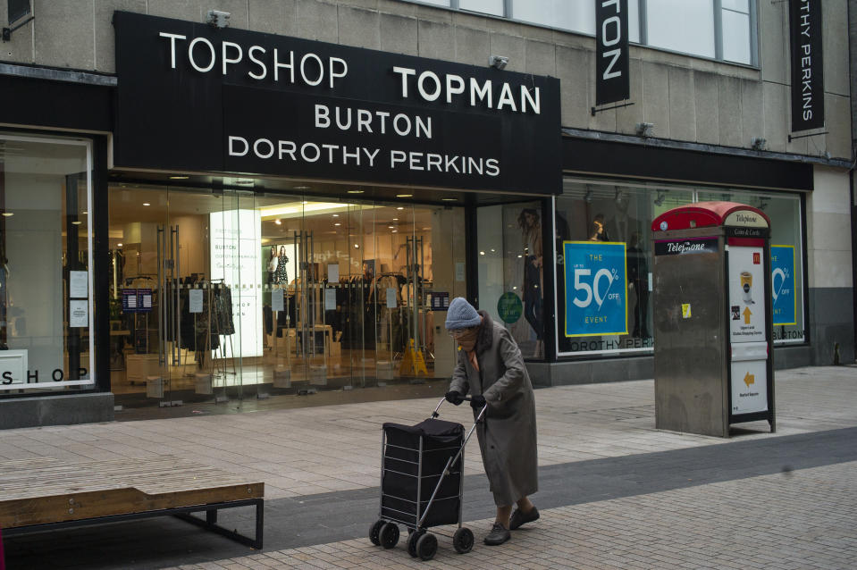 LONDON, ENGLAND - NOVEMBER 30: An elderly woman wearing a face mask walks past a store encompassing Topshop, Topman, Burton and Dorothy Perkins on November 30, 2020 in London, England. Sir Philip Green's retail empire Arcadia, which includes Topshop, Burton, Dorothy Perkins, Evans and Wallis is facing entering administration today putting 13,000 jobs at risk. (Photo by Dan Kitwood/Getty Images)
