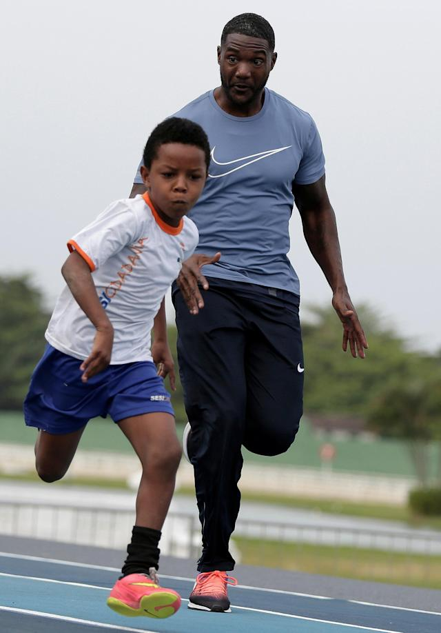 "Justin Gatlin of the U.S. runs with a child from the Mangueira slum ahead of the ""Mano a Mano"" challenge, a 100-meter race, at the Brazilian Jockey Club in Rio de Janeiro, Brazil, September 29, 2017. REUTERS/Bruno Kelly"