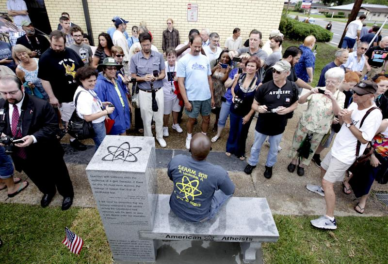 People gather around to sit and take photos during the unveiling of an Atheist monument outside the Bradford County Courthouse on Saturday, June 29, 2013 in Stark, Fla. The New Jersey-based group American Atheists unveiled the 1,500-bound granite bench Saturday as a counter to the religious monument in what's called a free speech zone. Group leaders say they believe it's the first such atheist monument on government property. About 200 people attended the event.(AP Photo/The Gainesville Sun, Matt Stamey)