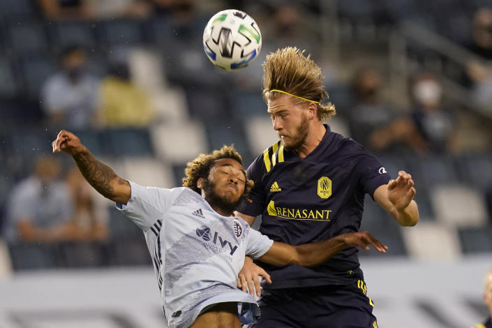 CORRECTS TO NASHVILLE SC'S WALKER ZIMMERMAN NOT RANDALL LEAL - Nashville SC's Walker Zimmerman, right, heads the ball over Sporting Kansas City forward Gianluca Busio, left, during the first half of an MLS soccer match in Kansas City, Kan., Sunday, Oct. 11, 2020. (AP Photo/Orlin Wagner)