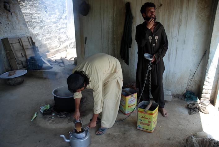 Chained Pakistani drug addicts make tea at a brutal addiction centre run by a local cleric in Haripur on July 19, 2014 (AFP Photo/Shakil Ahmad)