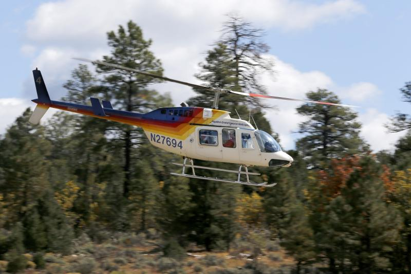 In this Oct. 11, 2013 photo, a tour helicopter takes off at Grand Canyon National Park Airport in Tusayan, Ariz. Air tour operators that use aircraft with quiet technology will be able to fly more people over the Grand Canyon. The Federal Aviation Administration said it plans to release 1,721 flight allocations this year that had been abandoned to those commercial tour operators, as long as their active fleet doesn't increase noise in the park overall. (AP Photo/Ross D. Franklin)