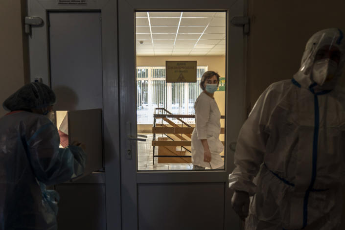 A nurse walks past a red zone as medical workers wearing special suits to protect against coronavirus work there in central district hospital of Kolomyia, western Ukraine, Tuesday, Feb. 23, 2021. After several delays, Ukraine finally received 500,000 doses of the AstraZeneca vaccine marketed under the name CoviShield, the first shipment of Covid-19 vaccine doses. The country of 40 million is one of the last in the region to begin inoculating its population. (AP Photo/Evgeniy Maloletka)
