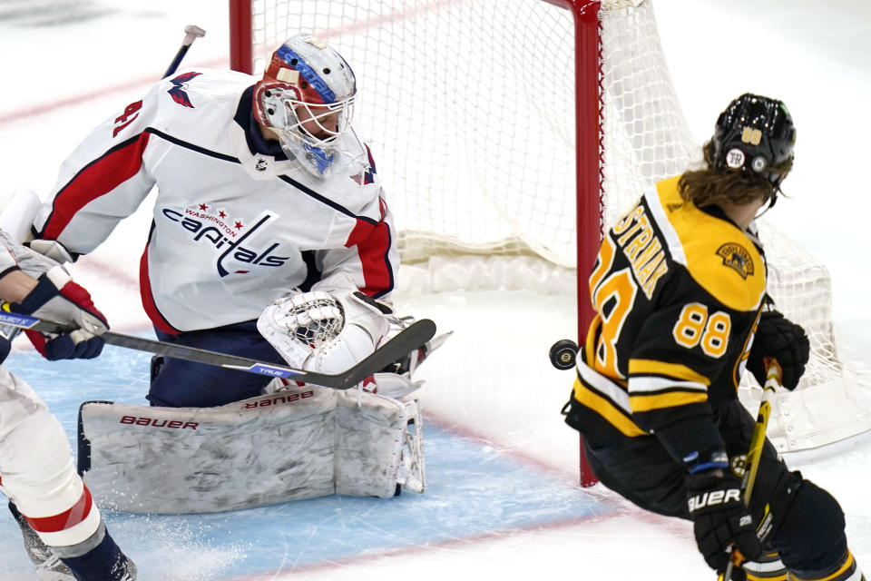 Washington Capitals goaltender Vitek Vanecek, looks back as the puck hits the post after a shot by Boston Bruins right wing David Pastrnak (88) during the first period of an NHL hockey game, Wednesday, March 3, 2021, in Boston. (AP Photo/Charles Krupa)