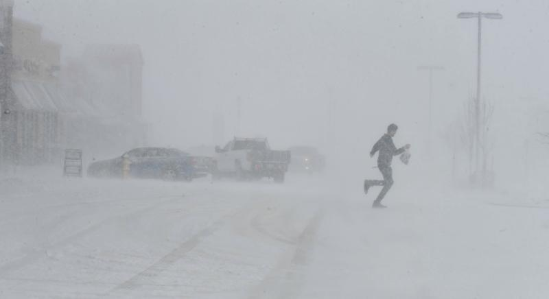 Clutching a bag of groceries a man sprints to his car as he leaves the Sprouts grocery store on North Gate Blvd. in Colorado Springs, Colo. At that time, the store was still open while a massive blizzard was moving through on Wednesday, March 13, 2019. Some of Colorado's busiest highways are closed as a raging storm brings heavy snow to a wide swath of the West and Midwest. Many schools and state offices were shut down Wednesday amid a blizzard expected to engulf parts of Colorado, Wyoming, Montana, Nebraska and South Dakota. (Jerilee Bennett/The Gazette via AP)