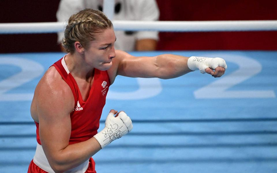 Britain's Lauren Price (red) celebrates after winning against Panama's Atheyna Bylon after their women's middle (69-75kg) quarter-final boxing match during the Tokyo 2020 Olympic Games at the Kokugikan Arena in Tokyo on July 31, 2021 - AFP/LUIS ROBAYO