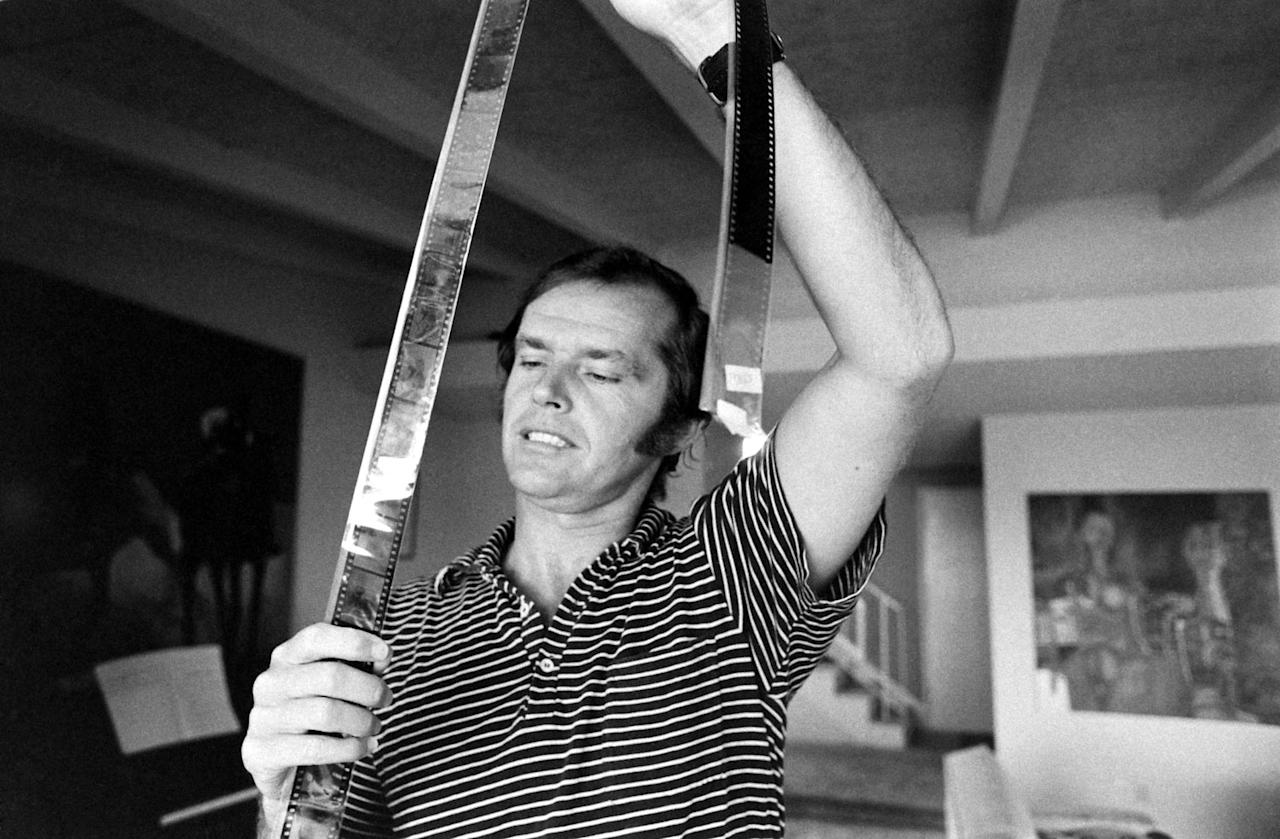 Not published in LIFE. Jack Nicholson looks at film negatives at his home, Los Angeles, 1969.