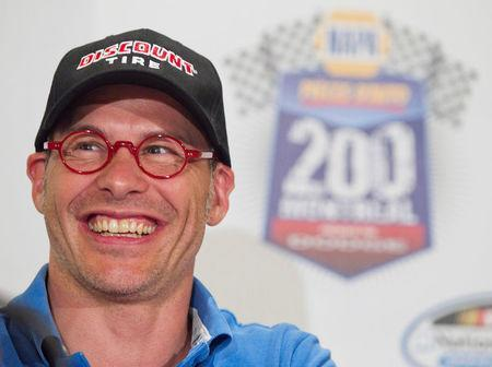 FILE PHOTO: Canadian race car driver Jacques Villeneuve smiles as he speaks to the media prior to the NAPA Auto Parts 200 Nationwide Series NASCAR race in Montreal, August 18, 2011. REUTERS/Christinne Muschi/File Photo