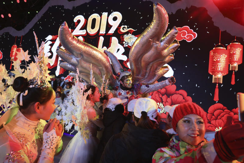 Performers take selfies at the end of a countdown to the new year event in Beijing, China
