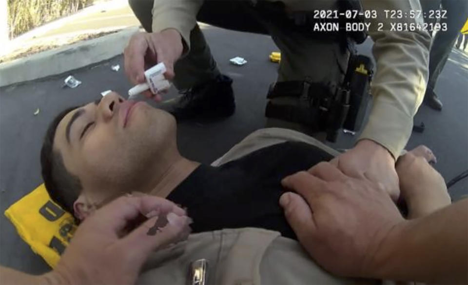 """In this image taken from police body camera video and provided by the San Diego County Sheriff's Department, San Diego County Sheriff's Deputy David Faiivae gets aid from an officer, after being exposed to fentanyl on July 3, 2021 in San Diego. A public safety video that told viewers the deputy had a near-death experience after being exposed to fentanyl used the actual footage, the San Diego Sheriff's department said Monday, Aug. 9, 2021, after critics questioned the deputy's severe reaction. The video shows """"an actual incident involving the deputy as he processed a white powdery substance that tested positive for Fentanyl,"""" a department news release said. (San Diego County Sheriff's Department via AP)"""
