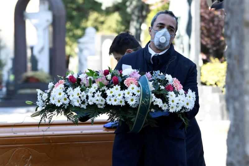 FILE PHOTO: Cemetery workers and funeral agency workers in protective masks transport a coffin of a person who died from coronavirus disease (COVID-19), into a cemetery in Bergamo