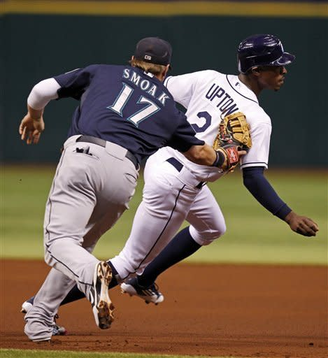 Tampa Bay Rays' B.J. Upton, right, is tagged out by Seattle Mariners first baseman Justin Smoak after being picked off during the first inning of a baseball game Saturday, July 21, 2012, in St. Petersburg, Fla. (AP Photo/Mike Carlson)