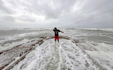 Luis Perez watches waves crash again a jetty in Galveston, Texas as Hurricane Harvey intensifies in the Gulf of Mexico Friday, Aug. 25, 2017 - Credit: AP