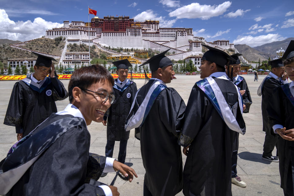 Graduates of the College of Science of Tibet University gather to pose for a group photo at the base of the Potala Palace in Lhasa in western China's Tibet Autonomous Region, as seen during a rare government-led tour of the region for foreign journalists, Tuesday, June 1, 2021. Long defined by its Buddhist culture, Tibet is facing a push for assimilation and political orthodoxy under China's ruling Communist Party. (AP Photo/Mark Schiefelbein)