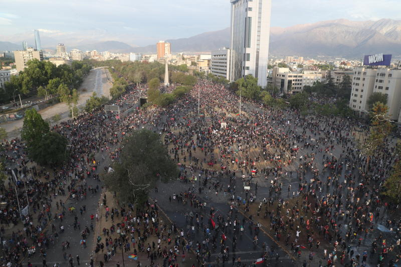 People gather for an anti-government protest in Santiago, Chile Friday, Nov. 1, 2019.  Groups of Chileans continued to demonstrate as government and opposition leaders debate the response to nearly two weeks of protests that have paralyzed much of the capital and forced the cancellation of two major international summits. (AP Photo/Esteban Felix)