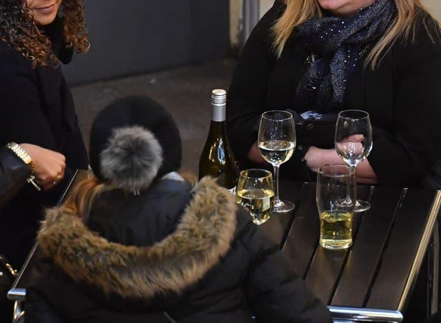 A group of women drinking white wine outside a bar