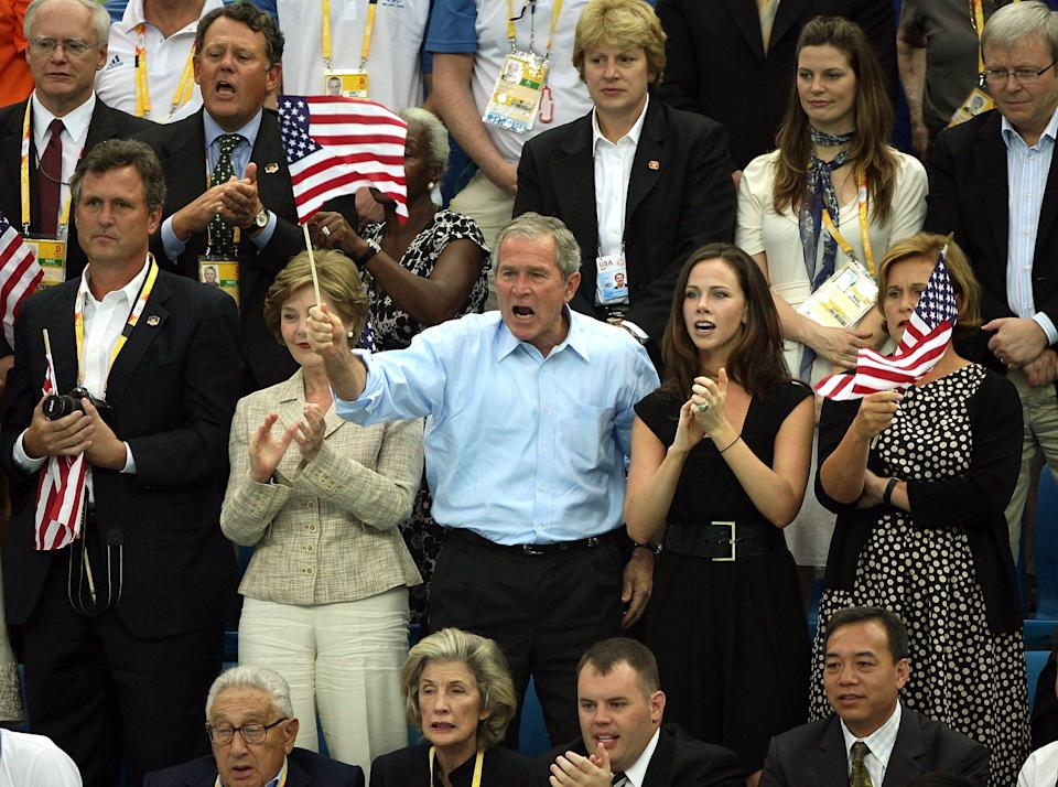 President George W. Bush, first lady Laura Bush and daughter Barbara Bush cheer on the American team at the swimming arena at the National Aquatics Center at the Beijing 2008 Olympic Games on August 10, 2008.