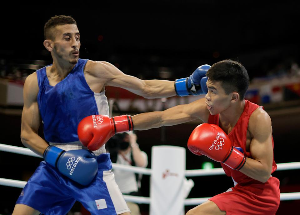 TOKYO, JAPAN - JULY 31: Carlo Paalam (red) of Team Philippines exchanges punches with Mohamed Flissi of Team Algeria during the Men's Fly (48-52kg) on day eight of the Tokyo 2020 Olympic Games at Kokugikan Arena on July 31, 2021 in Tokyo, Japan. (Photo by Ueslei Marcelino - Pool/Getty Images)