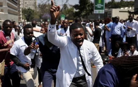 Doctors sing and hold placards during a protest over the disappearance of the leader of their union in Harare