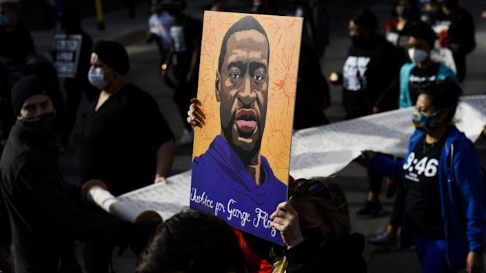 Demonstrators carry a scroll listing the names of people killed by police during a march in honor of George Floyd in Minneapolis in 2021. (Photo by Stephen Maturen/Getty Images)