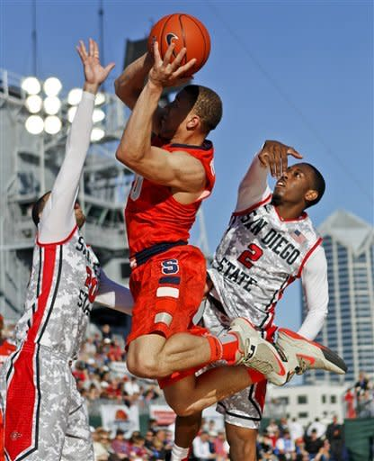 Syracuse 's Brandon Triche shoots between San Diego State's JJ O'Brien, left, and Xavier Thames during the second half of Syracuse's 62-49 victory in an NCAA college basketball game on the deck of the USS Midway, Sunday, Nov. 11, 2012, in San Diego. (AP Photo/Lenny Ignelzi)