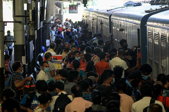 Sri Lankan commuters wearing face masks get in to the train at the Fort Railway Station, Colombo, Sri Lanka.