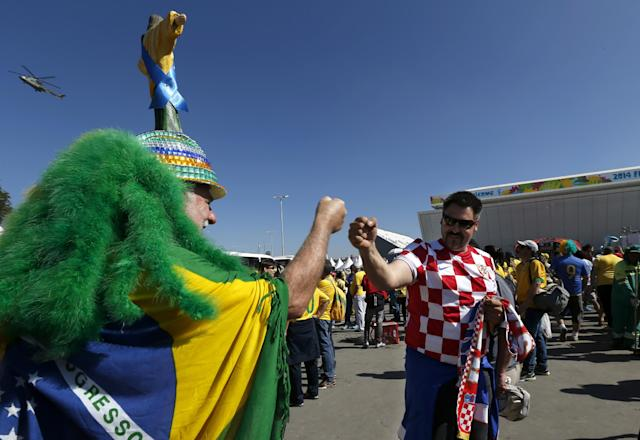 "Brazilian soccer fan Amaceo Jgussi, left, fist bumps with Croatian fan Robert Krnezic, as they wait to enter the Itaquerao Stadium to watch the World Cup opening match, between Brazil and Croatia of group A, in Sao Paulo, Brazil, Thursday, June 12, 2014. Thursday is a holiday in Sao Paulo and everybody is celebrating the start of the international soccer tournament. Fans dressed in yellow and green greeted each other, often yelling, ""Vai Brazil!"" (AP Photo/Julio Cortez)"
